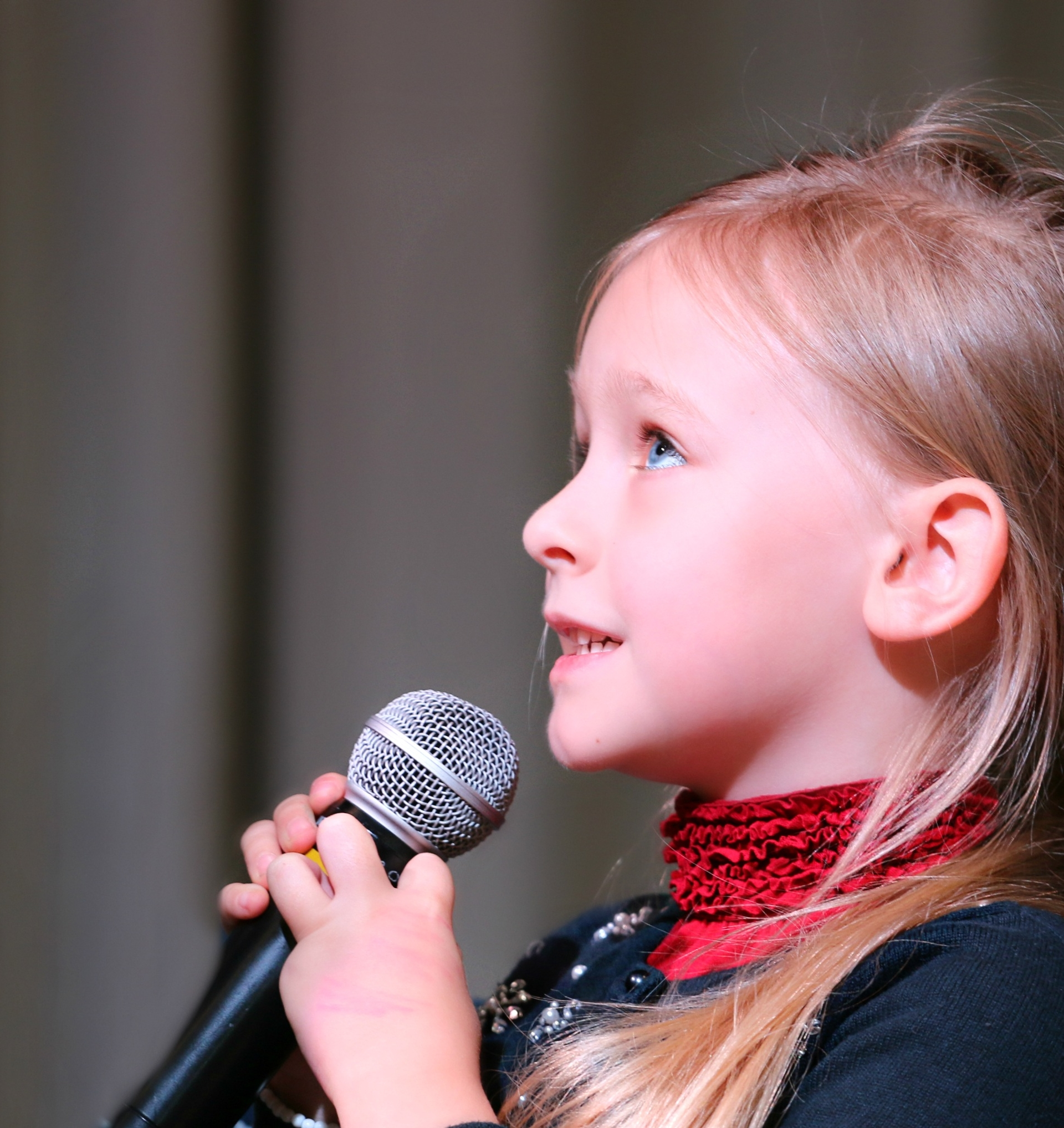 A young girl taking singing lessons